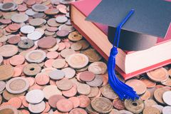 Graduation cap and books on many coins - Money saving for educat. Ion concept Royalty Free Stock Photography