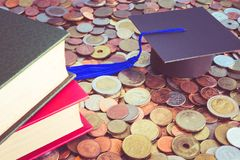 Graduation cap and books on many coins - Money saving for educat. Ion concept Stock Photos