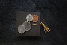 Graduation cap with coins. Small graduation cap with assorted coins, on dark background Royalty Free Stock Photo