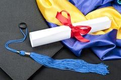 Graduation cap and diploma. A graduation setting with cap,tassel, gown, hood and diploma Stock Photos