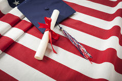 Graduation Cap and Diploma Resting on American Flag Stock Photos
