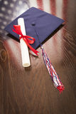Graduation Cap and Dipoma on Table with American Flag Reflection Royalty Free Stock Photo