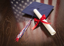 Graduation Cap and Dipoma on Table with American Flag Reflection Stock Image