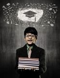 Graduation Cap. Genius Boy Holding Books Wearing Glasses,  Chalk. Cute Intelligent Little Boy Holding Books And Wearing Glasses, Smiling While Standing Before A Stock Photo