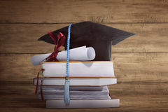 Graduation cap with graduation paper on a stack of book. Over wooden background royalty free stock photos