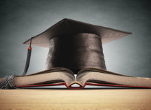 Graduation. Cap over the book with blackboard on background. Clipping path included Royalty Free Stock Photos