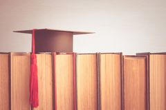 Graduation cap over the books on white wall background - Educati. On concept Royalty Free Stock Photo