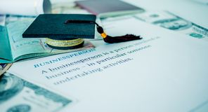 Graduation cap on passport and letter book, Businessperson, Concept of graduate education MBA abroad in university, requires a lo. T foreign currency Dollars to stock image