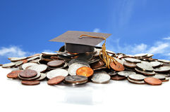Graduation cap on a pile of coins Royalty Free Stock Image
