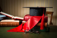 Graduation cap and red ribbon lying on books at library Royalty Free Stock Images