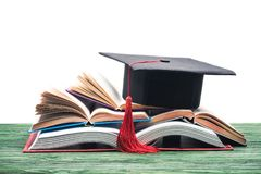 Graduation cap on stack of. Open books royalty free stock image