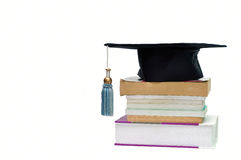 Graduation cap on top of a stack of books. Isolated on white Royalty Free Stock Images