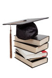 Graduation cap on top of a stack of books on white. A graduation cap on top of a stack of books on a white background Stock Photos
