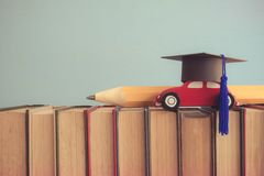 Graduation cap, wooden car and big pencil over the books on blue. Wall background - Education concept Stock Photos