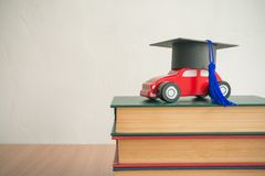 Graduation cap on wooden car over the pile of books on white wal. L background - Education concept Royalty Free Stock Images