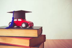 Graduation cap on wooden car over the pile of books on white wal. L background - Education concept Stock Photography