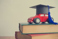 Graduation cap on wooden car over the pile of books on white wal. L background - Education concept, Retro tone Royalty Free Stock Image