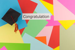 Graduation cap and word on colorful paper background Stock Images