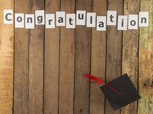 Graduation cap and word on wooden background Royalty Free Stock Photos