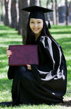 Graduation Celebration. The girl the graduate of university with the diploma in hands, in park Stock Photo