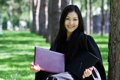 Graduation Celebration. The girl the graduate of university with the diploma in hands, in park Stock Photos