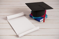 Graduation ceremony announcement concept. Mortarboard, books and empty paper scroll on wooden surface. Graduation ceremony announcement concept. 3D Rendering Royalty Free Stock Photo