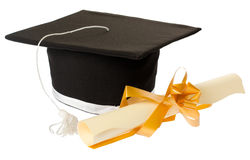 Graduation concept. Black graduation hat next to a diploma tied with a ribbon, isolated on white Stock Images