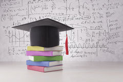 Graduation concept. Abstract graduation hat and colorful book pile placed on concrete surface. Wall with mathematical formulas in the background. Graduation Stock Image
