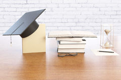 Graduation concept brick background. Graduation concept with books, graduation cap, hourglass and spectacles on wooden desktop with brick wall in the background Royalty Free Stock Images