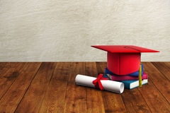 Graduation concept. Red mortarboard, books and diploma placed on wooden surface and concrete wall background. Graduation concept. 3D Rendering Royalty Free Stock Images