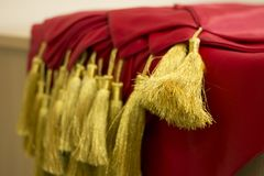 The Graduation Cords. Gold graduation cords and red scarfs graduate accessories background with space for text royalty free stock photos