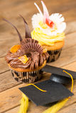 Graduation cupcakes on wooden table Stock Photography