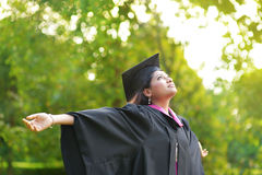 Graduation day. Young Asian Indian female student open arms outdoor on graduation day Stock Image