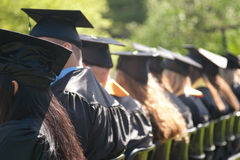 Graduation Day is Here!. Students at an outdoor university commencement ceremony. The image orientation is horizontal and there is copy space Royalty Free Stock Images