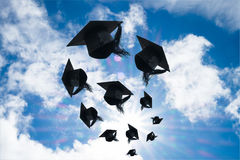 Graduation day, Images of graduation Caps or hat throwing in the. Air with sunshine day on blue sky background, Happiness feeling, Commencement day Stock Photo