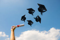 Graduation day, Images of hand holding a certificate and Caps or Royalty Free Stock Photo