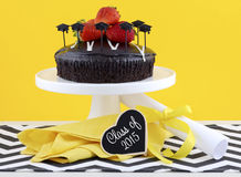 Graduation Day Party with Chocolate Cake. Happy Graduation Day yellow, black and white theme party with chocolate cake and strawberries Stock Image
