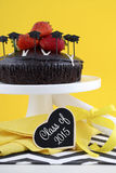 Graduation Day Party with Chocolate Cake. Happy Graduation Day yellow, black and white theme party with chocolate cake and strawberries Stock Photography