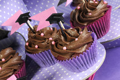 Graduation day pink and purple party cupcakes - angle close up. Graduation day pink and purple party chocolate cupcakes with small graduation cap toppers on Stock Photography