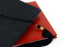 Graduation diploma and cap. Black graduation cap with tassle on top of red diploma Royalty Free Stock Photography