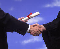 Graduation diploma and handshake Royalty Free Stock Photos