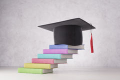Graduation and education concept. Abstract graduation hat and colorful book ladder placed on concrete background. Graduation and education concept. 3D Rendering Royalty Free Stock Photos