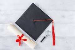 Graduation equipment. Mortarboard, magnifying glass and diploma tied with red ribbon on white wooden table, top view royalty free stock images
