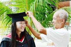 Graduation. Father adjusting mortarboard for daughter on her university graduation day Stock Photos