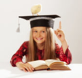 Graduation girl. Portrait of little clever girl with chick on her grad cap Stock Photo