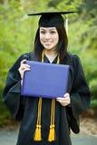 Graduation girl. A happy beautiful graduation girl holding her diploma Royalty Free Stock Photography