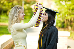 Graduation girl. A happy beautiful graduation girl being congratulated by her friend Royalty Free Stock Images
