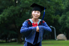 Graduation girl. In a blue graduation gown, making a bow with hands folded in front Stock Photography
