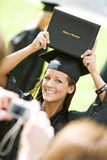 Graduation: Girl Holds Up College Diploma for Camera. Extensive series of recent student graduates after graduation, outside with friends. Muti-ethnic group royalty free stock images