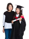 Graduation girl with older sister. Isolated on white Stock Images